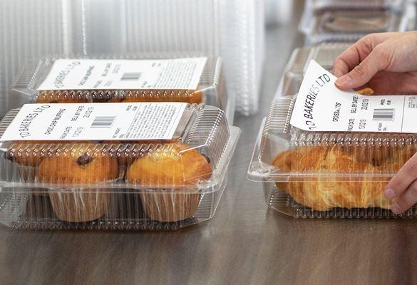 Hände kleben Brother Lebensmitteletikett auf vorverpackte Lebensmittel, Muffins und Croissants