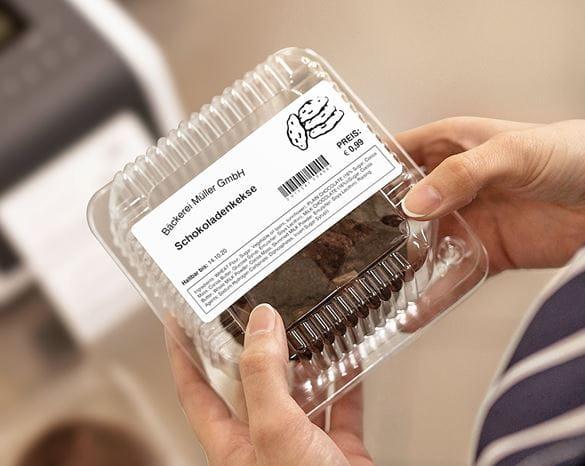 Hände halten vorverpackte Cookies, Brotehr Lebensmitteletikett auf Plastik-Umverpackung