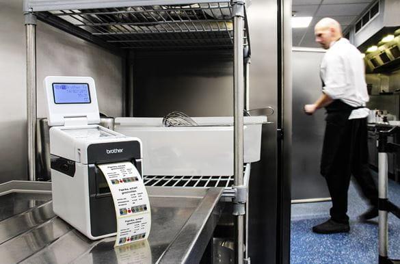 TD-Etikettendrucker druckt Warenrotationsetiketten in Restaurant-Küche, Koch im Hintergrund an Kühlschrank