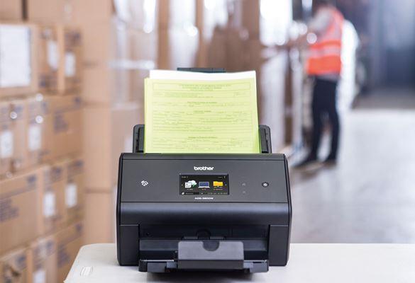 Brother ADS-3600W Desktop-Scanner auf Tisch zur Archivierung von Versandscheinen in einem Lager, Kisten, Mann in Schutzweste