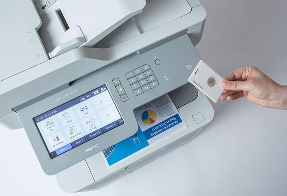 Die Hand einer Person hält eine NFC-Karte gegen einen Brother-Multifunktionsdrucker mit großem Bildschirm