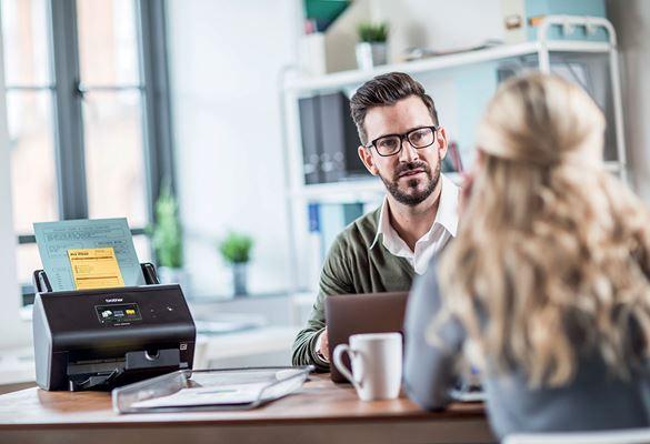 Mann mit Brille und Pullover sitzt am Schreibtisch mit Brother-Scanner und Kundin mit langen Haaren sitzt auf der gegenüberliegenden Seite