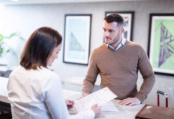 Frau mit braunen Haaren und weißem Hemd hält Papier hinter dem Kundenschalter, Mann mit braunem Pullover und weißem Hemd vor dem Kundenschalter