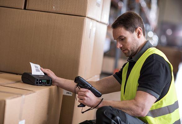 Mann in Warnweste hält Scanner, der Etiketten druckt, Etikettendrucker auf Kisten im Lager