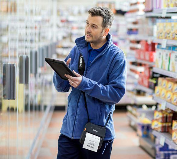 Lieferant überprüft mit Tabelt im Lebensmittelgeschäft die Waren am Kühlregal. Brother RJ-4-Drucker am Schultergurt