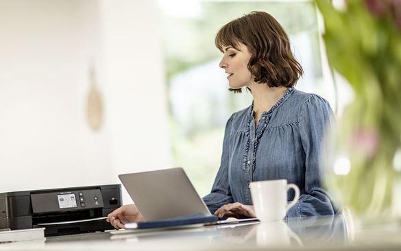 Eine Frau sitzt im Wohnraum am Laptop und nimmt eine Seite aus dem neben ihr stehenden schwarzen WLAN-Drucker.