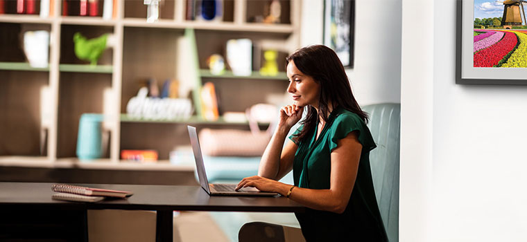 Woman with shoulder length brown hair in green sat using laptop at table, books, picture on wall, vase, ornaments