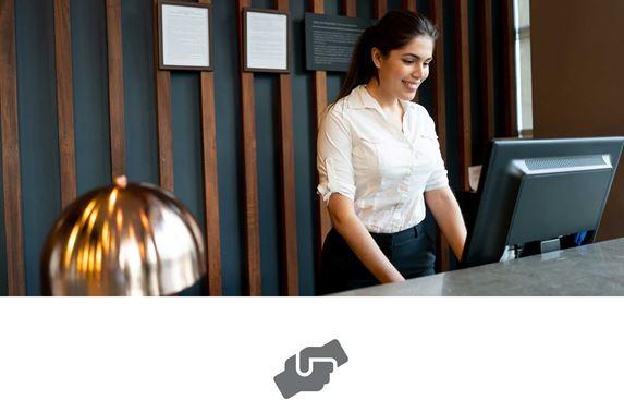 Weibliche Empfangsdame mit dunklen, zurückgebundenen Haaren und weißer Bluse, bedient einen Computer