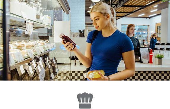 Frau mit dem blonden Haaren und blauem T-Shirt begutachtet Saftflaschen und Sandwiches