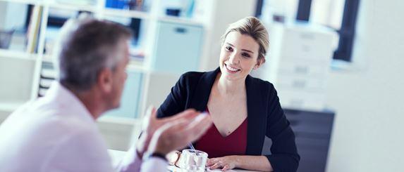 Frau und Mann an Tisch sitzend im Gespräch