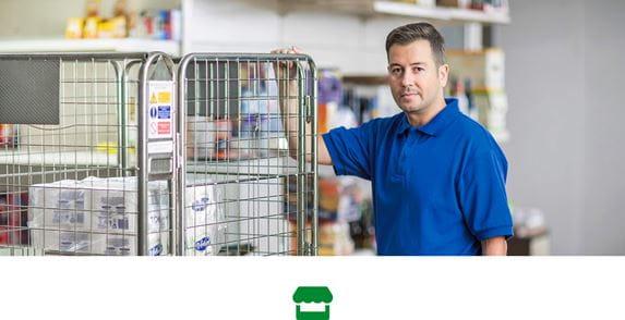 Mann in blauem Poloshirt hält sich an einem mobilen Transportmetallkäfig in einem Geschäft fest