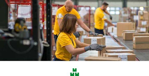 Frau und zwei Männer in gelben Poloshirts arbeiten im Lager an einem Förderband mit Kartonpaketen