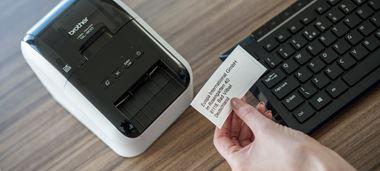 Person hält ausgedrucktes Etikett in der Hand, QL-Etikettendrucker auf Schreibtisch stehend