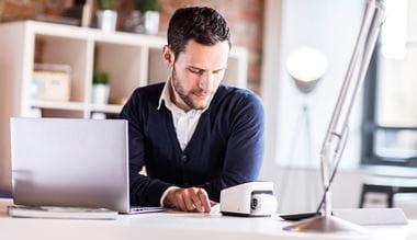Mann an Schreibtsich in Büro, vor VC-500W sitzend, druckt Etikett aus