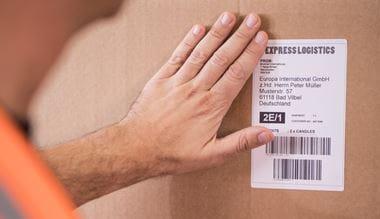 Logistik-Mitarbeiter klebt Brother Etikett an Paket