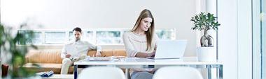 Frau an Schreibtisch sitzend mit Latop, Mann auf Couch im Hintergrund