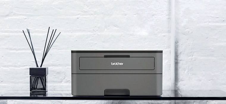 Dark grey mono laser printer HL-2350DW on a glass table with diffuser