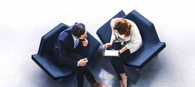 Mann und Frau, auf Loungemöbel sitzend, Vogelperspektive, im Gespräch mit iPad