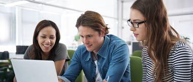 Gruppe Studenten im Gespräch, in Laptop schauend