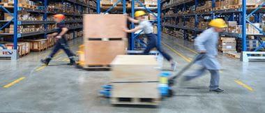 Logistikmitarbeiter befördern Waren in Lagerhalle
