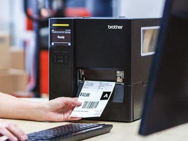 Mitarbeiterin sitzt an Schreibtisch und druckt Versandetikett an TJ-Industriedrucker