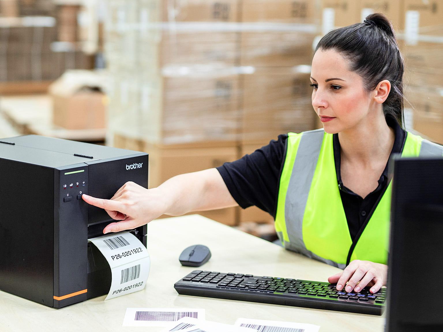 Logistikmitarbeiterin, an Schreibtisch sitzend, druckt Etiketten mit industriellem TJ-Etikettendrucker, Pakete auf Paletten im Hintergrund