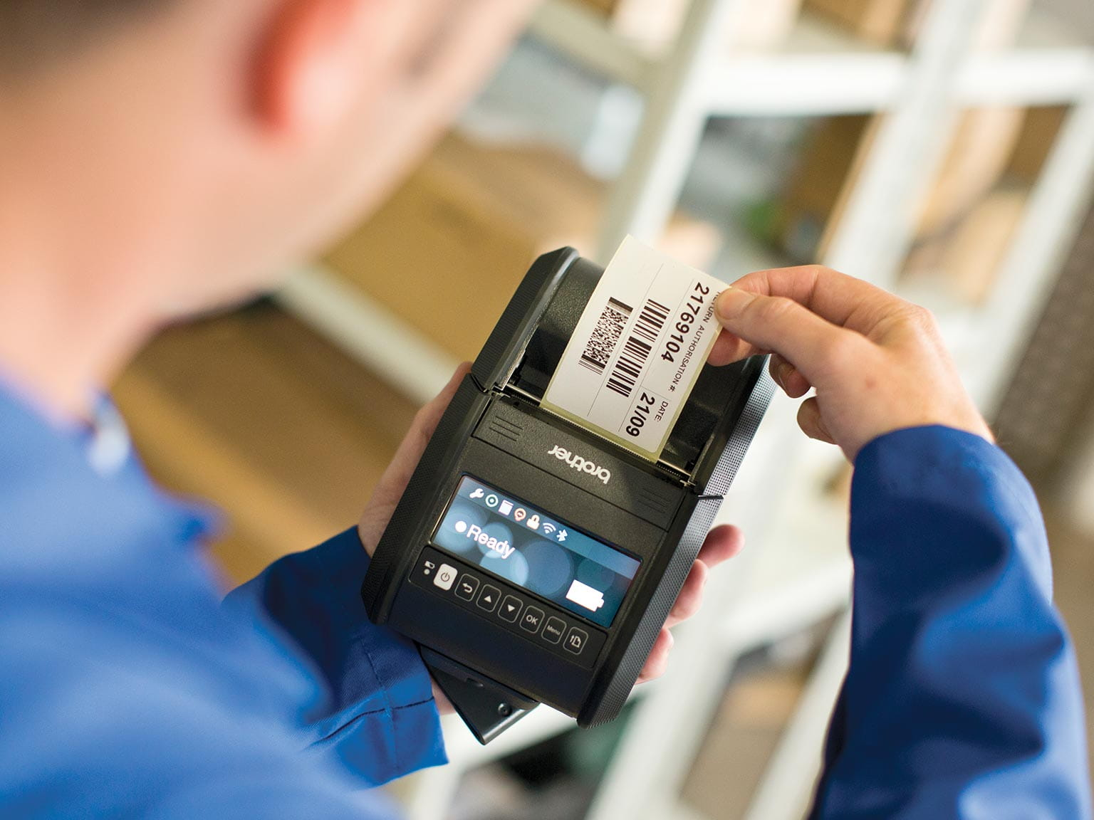 A warehouse worker holds an RJ series label printer in their hand whilst a label is being printed
