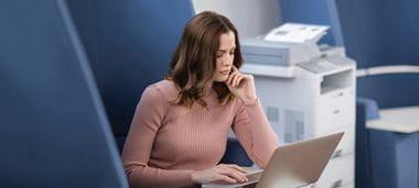 Frau in Office-Umgebung, an Laptop sitzend, Brother Drucker im Hintergrund