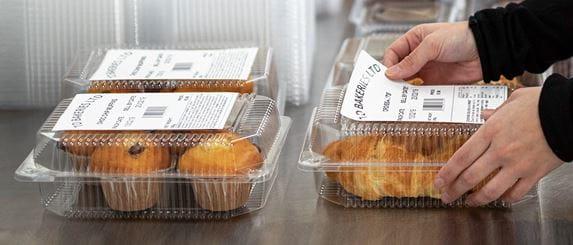 Hände bringen Brother Etiketten auf Plastikverpackung auf, Muffins und Croissants