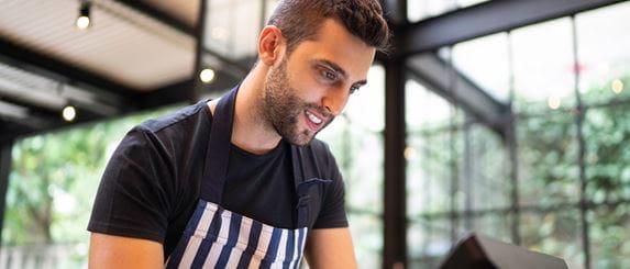 Restaurantmitarbeiter, lächelnd bedient Kassee, Restaurant im Hintergrund