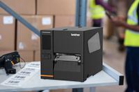 Brother TJ Industrie-Etikettendrucker auf Arbeitsplatte mit bedruckten Etiketten und Scanner im Lager