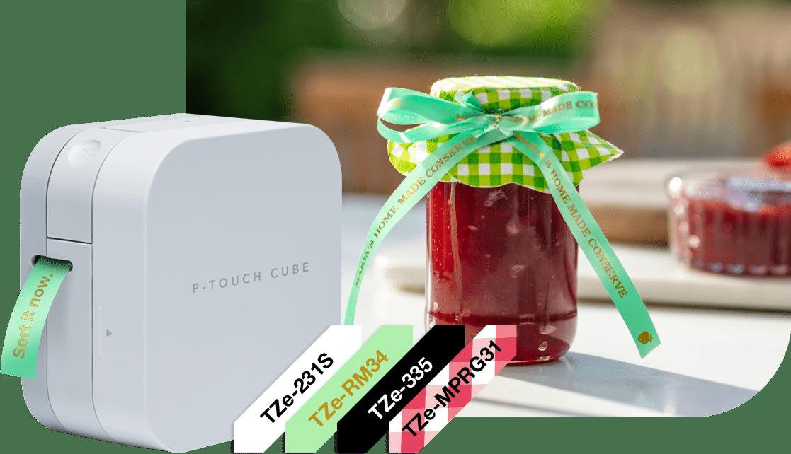 P-touch CUBE mit grünem Textiletikett, TZe-Schriftbänder daneben, Marmeladenglas mit grünem Textilband im Hintergrund