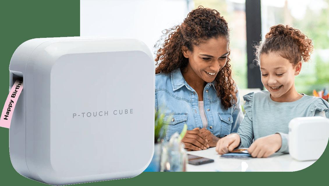 P-touch CUBE Plus (weißes Modell), im Hintergrund Frau und Mädchen, an Tisch sitzend, dekorieren Glückwunschkarte mit Schriftbändern und CUBE Plus