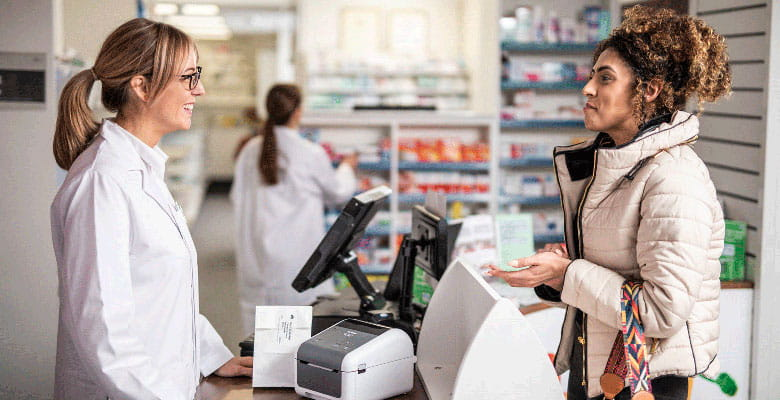 Pharmacist talking to customer over counter with Brother TD desktop printer