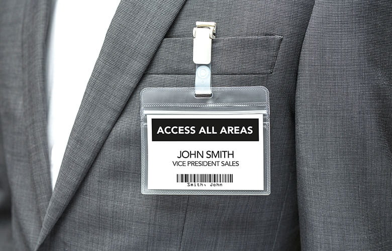 Visitor badge attached to person wearing grey suit jacket