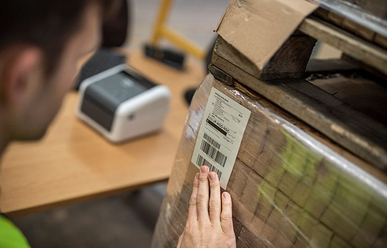 Shipping label being applied to boxes with Brother TD desktop label printer in background