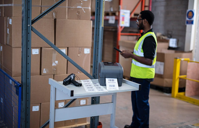 TD label printer printing labels on warehouse trolley with scanner