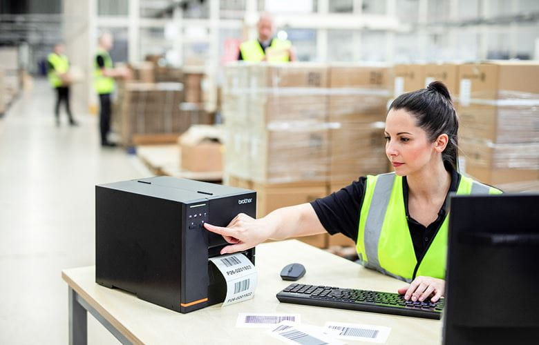 Logistikmitarbeiterin bedient TJ-Etikettendrucker, an Tisch sitzend in Lagerhalle
