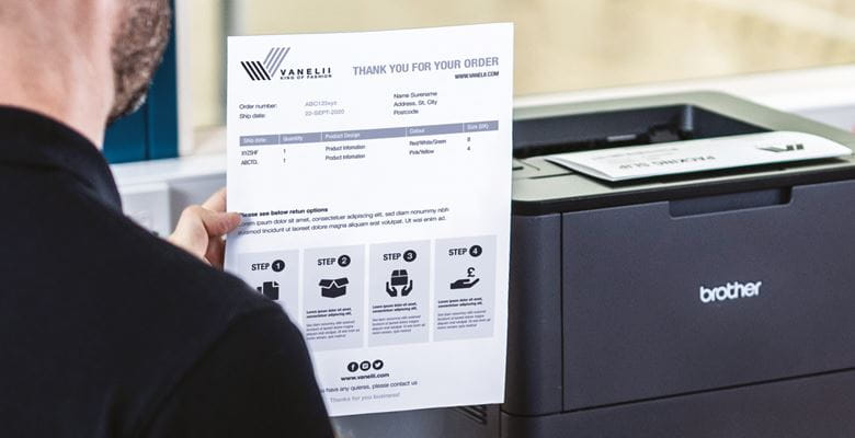Mann in schwarzem Polo-Shirt hält gedrucktes Dokument in der Hand, Brother Monolaserdrucker im Hintergrund auf Tisch stehend