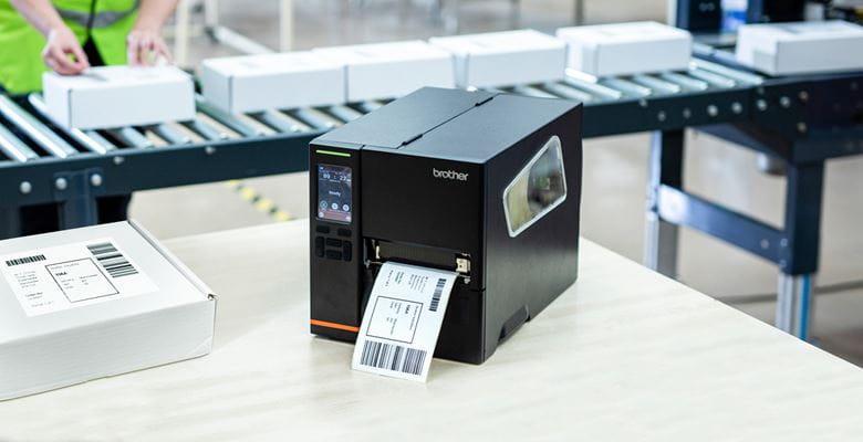 Brother-TJ-Etikettendrucker steht auf Tisch und druckt gerade Versandetikett aus, weißes äckchen daneben, im Transportband mit Päckchen
