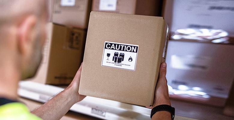 Mann hält braunen Karton mit Warnhinweisetikett