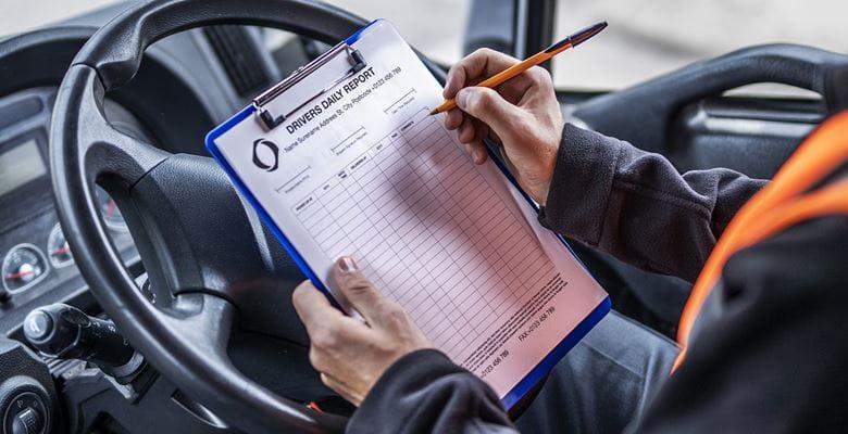 LKW-Fahrer füllt auf Fahrerplatz ein Dokument auf einem Klemmbrett aus