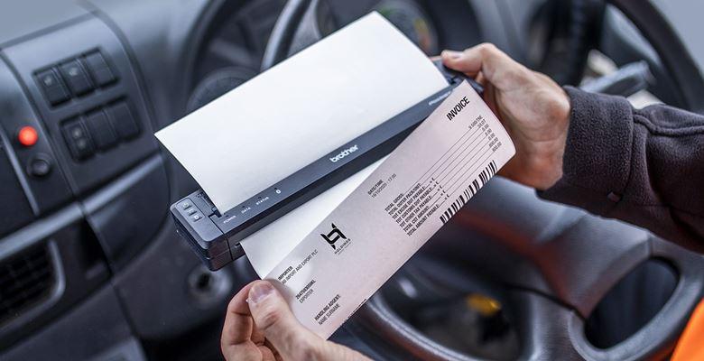 LKW-Fahrer druckt auf Fahrerplatz ein Dokument mit mobilem Drucker in seiner Hand aus