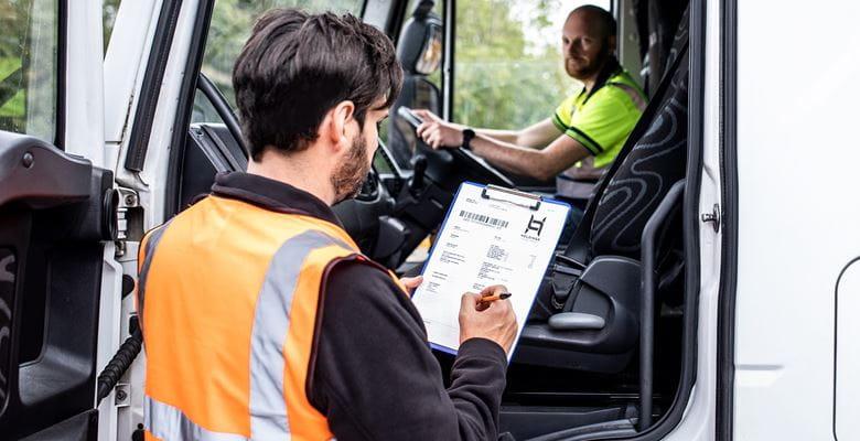 Fahrer sitzt im Lastwagen, an der offenen Tür steht ein Lagerarbeiter in orangener Warnweste und prüft die eingehende Lieferung