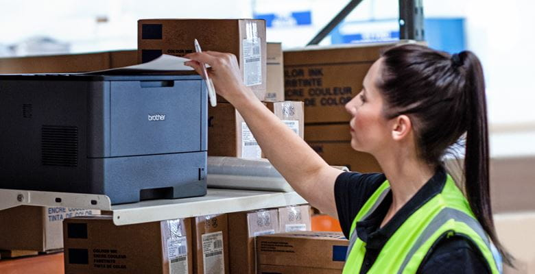 Frau in Warnweste, mit dunklen Haaren und Zopf, steht vor Lagerregal und nimmt Ausdruck aus Brother Monolaserdrucker, Pakete im Hintergrund