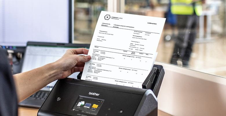 Frau im schwarzen Poloshirt führt in Lagerbüro Kommissionierliste mit Hand in Dokumentenscanner ein. Laptop, Bildschirm und Lagerarbeiter im Hintergrund