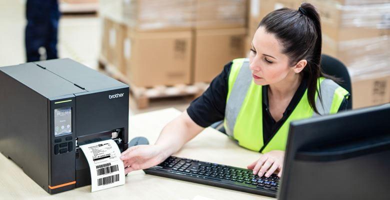 Frau in Warnweste sitzt an Schreibtisch und entnimmt Versandetikett aus TJ-Industriedrucker, Pakete im Hintergrund