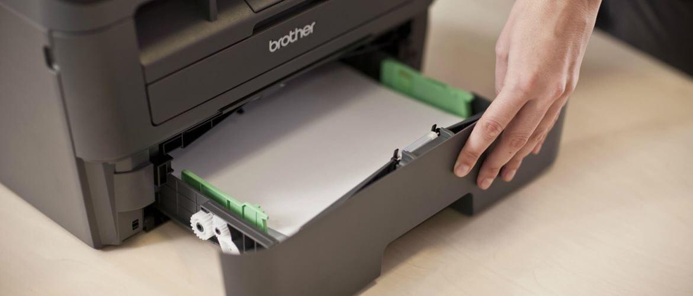 Persona rellenando papel en bandeja de impresora Brother