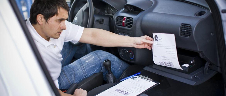 Hombre imprimiendo con impresora portátil en el coche
