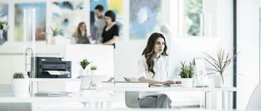 Mujer en oficina mirando pantalla de ordenador